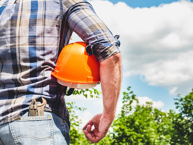Attractive man with tools, holding a safety helmet. view from the back, close-up. concept of work and employment