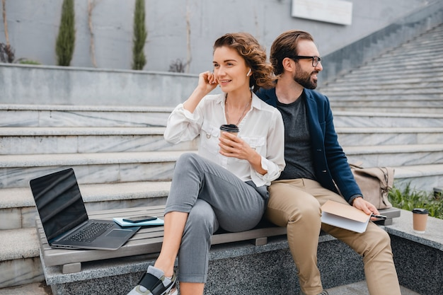 Attractive man and woman sitting on stairs in urban city center