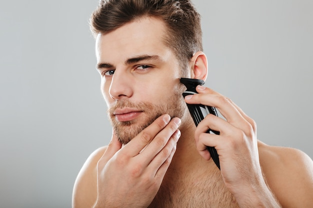 Attractive masculine male being undressed at home having skincare while shaving his face with trimmer against grey wall