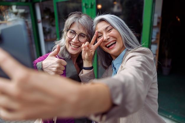 친구와 함께 매력적인 성숙한 아시아 여성은 도시 거리에서 전화로 몸짓으로 셀카를 찍습니다.