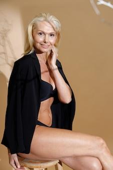 下着とカメラを見て上に古典的な黒のジャケットの魅力的な成熟したブロンドの女性