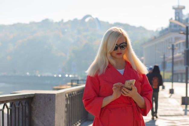 魅力的な成熟したブロンドの女性が携帯電話でメッセージを入力し、太陽の光でポーズをとる。コピースペース