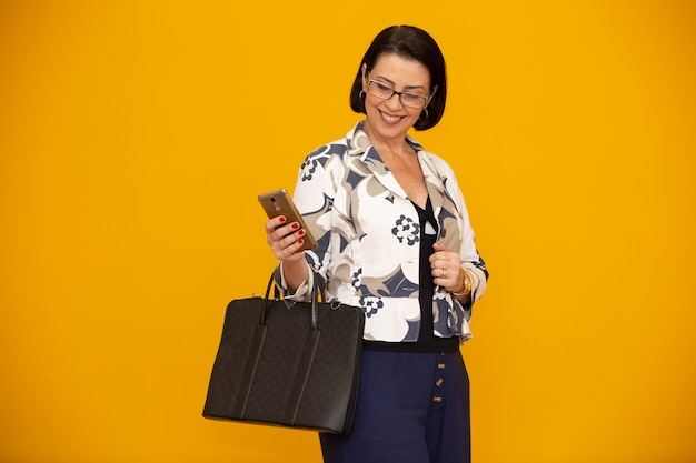 Attractive mature businesswoman working with her mobile phone