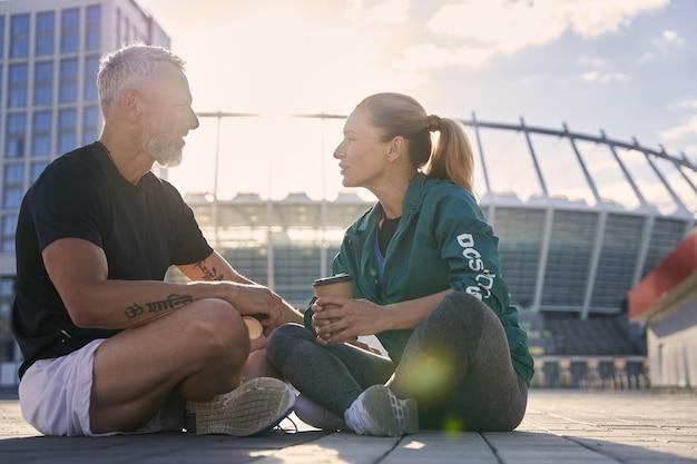 Привлекательная зрелая пара общается друг с другом во время отдыха на открытом воздухе после утренней тренировки