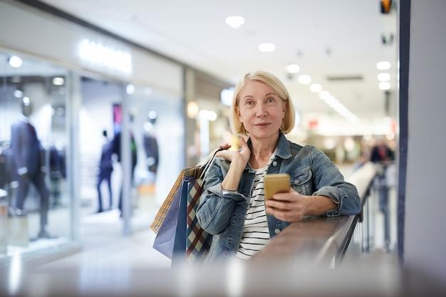 買い物中に友人に写真メッセージを送信する魅力的な成熟した女性