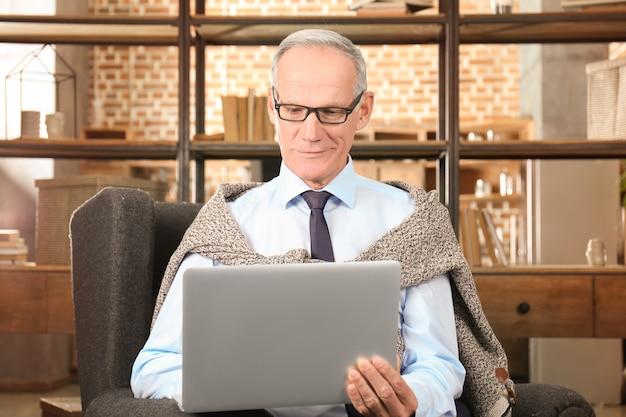 Attractive mature man using laptop indoors