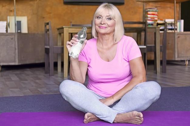 집에서 요가 매트에 물을 마시는 매력적인 성숙한 여자