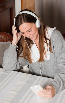 Attractive mature woman at home using mobile, wearing gray sweater and headphones, video conferencing, dog at home
