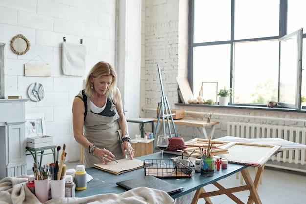 テーブルに立って、アートスタジオでスケッチに取り組んでいるエプロンの魅力的な成熟した女性