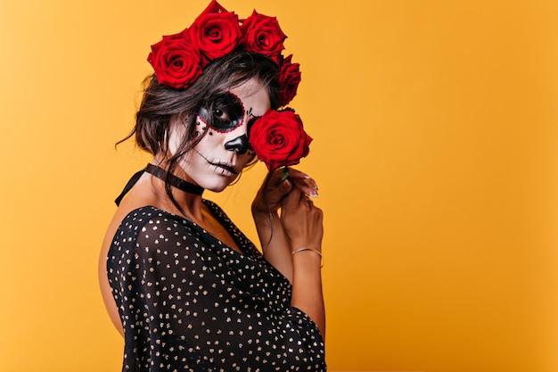 ハロウィーンの衣装で魅力的な成熟した女性はバラが大好きです。赤い花で目を閉じているメキシコの女性のクローズアップの肖像画。
