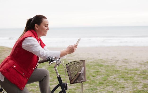 携帯電話のビーチの背景を使用して自転車で魅力的な成熟した女性