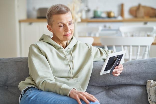 フレーム内の写真を見て、笑顔のソファに座っている魅力的な成熟した女性