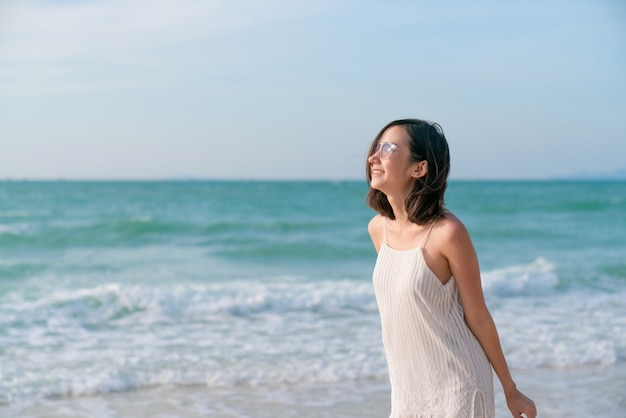 Attractive mature woman walking on the beach barefoot. beautiful female