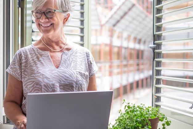 魅力的な成熟した女性の白い髪の笑顔は、ラップトップを使用して窓に座って、部屋の中を見ています。技術と社会を楽しむ眼鏡をかけている老婦人