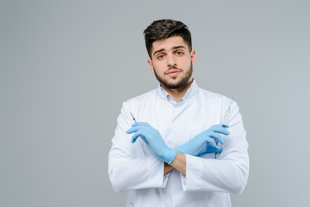 Attractive medical doctor in gloves with suringes isolated over grey background