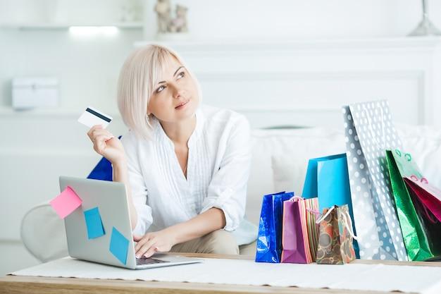 魅力的な30代の女性がオンラインショッピングをしています。女性がクレジットカードを保持し、屋内で買い物袋とラップトップに座っています。