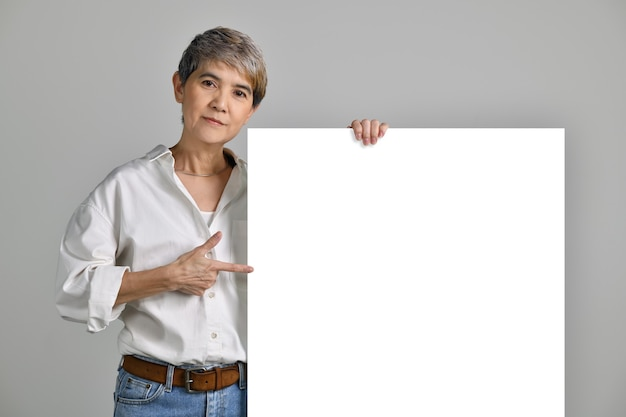 Attractive middle aged asian woman pointing fingers at blank signboard isolated on white background. looking at the camera