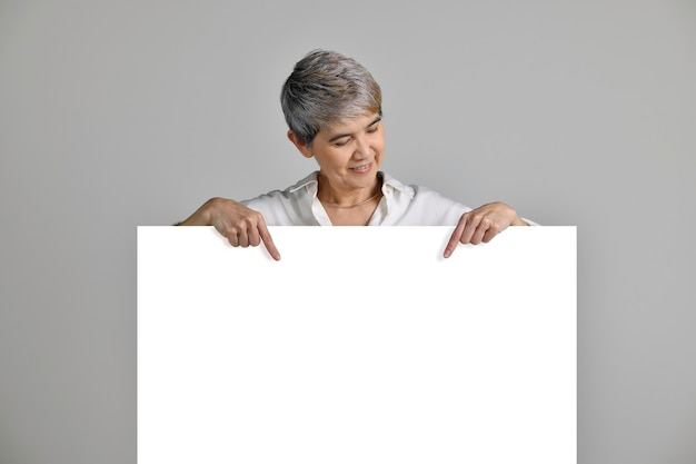 Attractive middle aged asian woman pointing fingers at blank signboard isolated on white background
