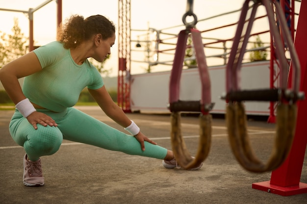 Attractive middle aged athlete woman doing warm-up, warming up before training outdoors in summer sportsground, kneading and stretching leg muscles. out of focus of suspension straps on the foreground