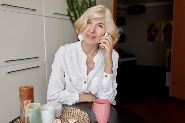 魅力的な中年のブロンドの女性が自宅の台所でリラックスして携帯電話で話している