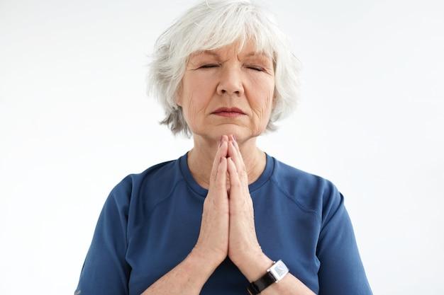 目を閉じて瞑想で手を一緒に押す魅力的な中年のヨーロッパの女性。穏やかな表情を持ち、呼吸法を練習し、瞑想するシニア白髪の女性