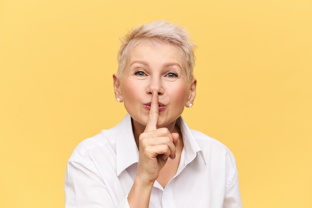 人差し指を口に持った白いシャツを着た魅力的な中年女性が、シッと言って、誰にも言わないで、秘密を守ってほしいと言って、不思議な表情をしている。