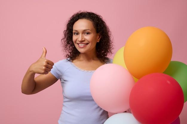 親指を立てて、こぼれるような笑顔で笑って、コピースペースでピンク色の背景に対してポーズをとってマルチカラーのエアボールを保持している青いtシャツの魅力的な中年ヒスパニック巻き毛の女性