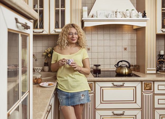 Attractive middle-aged woman drinks coffee with biscuits in kitchen.