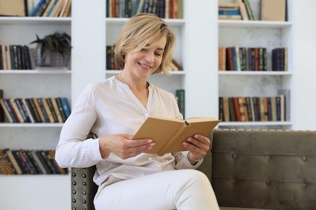 Привлекательная женщина средних лет, наслаждающаяся чтением книги, сидя на диване в своей гостиной, улыбаясь во время чтения.