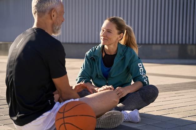 Привлекательная женщина средних лет в спортивной одежде разговаривает со своим мужем или другом-мужчиной во время отдыха