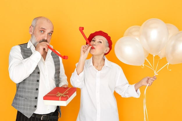 Attractive middle aged woman posing isolated with helium balloons with bearded senior male holding box of chocolate, blowing whistles