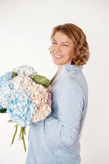 魅力的な中年女性の笑みを浮かべて、アジサイの花の花束を保持しています。コンセプトホリデー