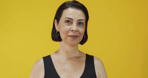 黄色の壁に美しい笑顔を持つ魅力的な中年女性。かなり年上の女性、成功した自信。