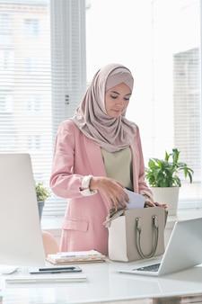 Привлекательная деловая женщина с ближнего востока в розовом хиджабе стоит за столом и упаковывает телефон в сумку, собираясь покинуть офис