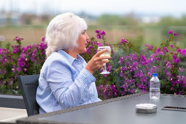 冷たいワインを飲みながらくつろぐ魅力的な中年女性