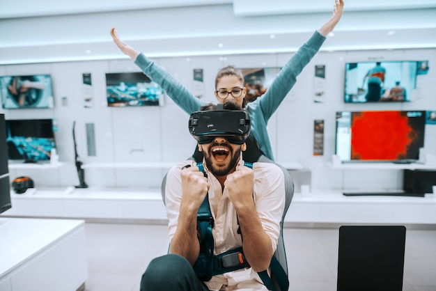 Attractive mixed race bearded man trying virtual reality technology while woman watching what is he doing. tech store interior.