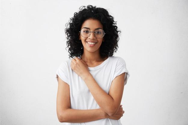 魅力的な混血の女性の女優が丸い眼鏡とtシャツを探して笑顔