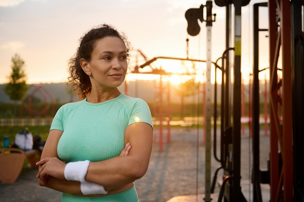 魅力的な混血、ゴージャスなヒスパニック系スポーツウーマン、目をそらし、日の出の朝に屋外ジムのマシンの背景に腕を組んで立っているスポーツウェアの女性アスリート。