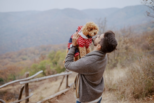 Attractive mixed race man holding his loving dog while standing in nature at fall.