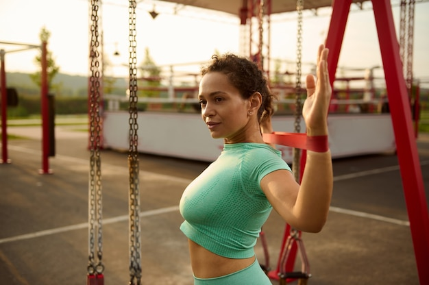 Attractive mixed race sporty woman working out outdoor in early morning at sunrise, doing exercises on shoulders and arms muscles, stretching her body with fitness elastic rubber band in sportsground