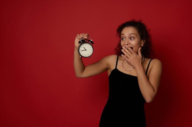 검은색 이브닝 드레스를 입은 매력적인 혼혈 여성이 손에 든 알람 시계를 보고 입을 가리고, 복사 공간이 있는 빨간색 배경 위에 격리됩니다. 새해 복 많이 받으세요 및 크리스마스 개념