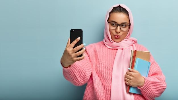 Attraente donna di razza mista con i capelli scuri, indossa copricapo di seta, tiene il cellulare davanti, scatta un selfie, pubblica un post nei social network, tiene due taccuini a spirale, prende il videomessaggio