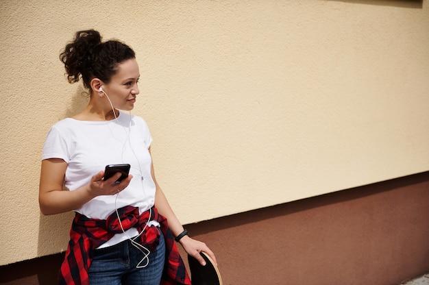 片手に携帯電話、もう片方の手にスケートボードを持ち、色付きの壁に背を向けて横を向いている、巻き毛の魅力的な混血の若い女性