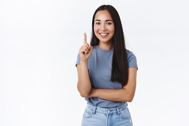 魅力的な現代のアジアのブルネットの女性は良い考えを持っています、指を上げてナンバーワンのルールを説明するか、最良の選択を示し、指摘し、何か重要なことを言っているように笑って、白い壁