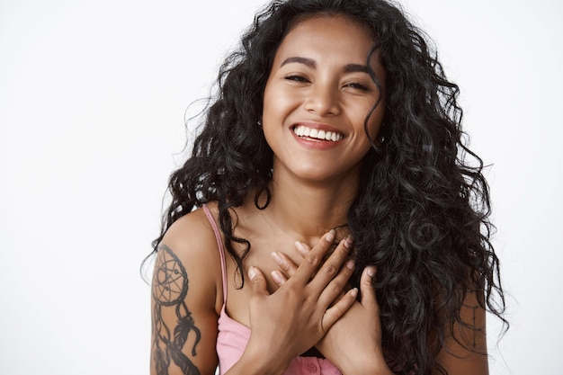 Attractive modern curly-haired woman with tattoos, hold hands on chest grateful and touched, laughing and smiling, enjoying touching lovely date, white wall