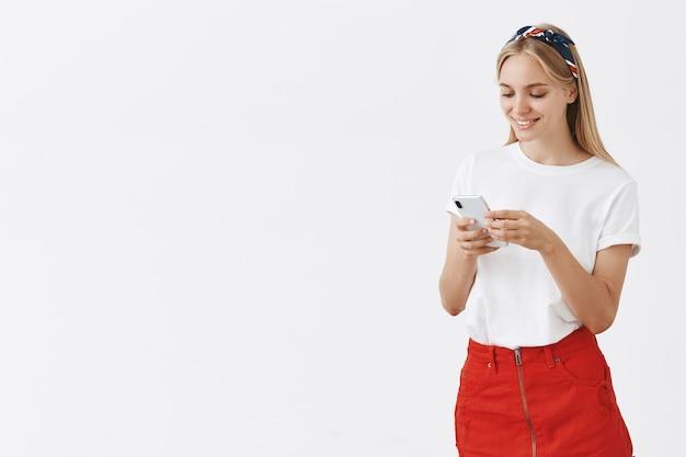 携帯電話を使用して笑顔で魅力的な現代の女の子