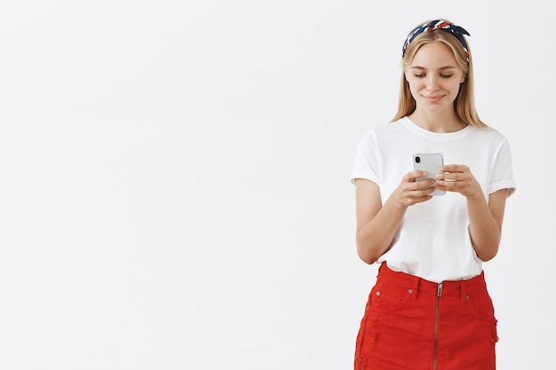 Attractive modern girl using mobile phone and smiling