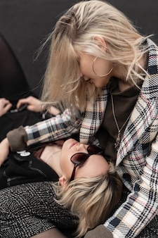 Attractive modern lesbians in fashionable casual retro clothes look at each other