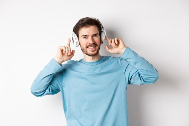 髭を生やした魅力的な現代人、笑顔、満足して、音楽を聴きながら頭の上のヘッドフォンに触れ、白い背景の上に立っています。