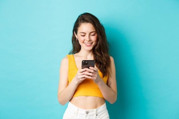 Привлекательная современная женщина разговаривает по мобильному телефону, глядя на экран с нежной улыбкой, обменивается сообщениями в приложении для знакомств, стоя на синем фоне.
